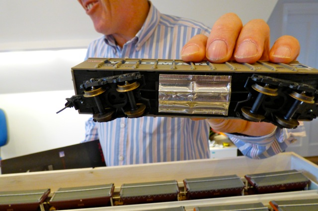 Aluminium Foil Tape on the bottom of a model train carriage - being fitted