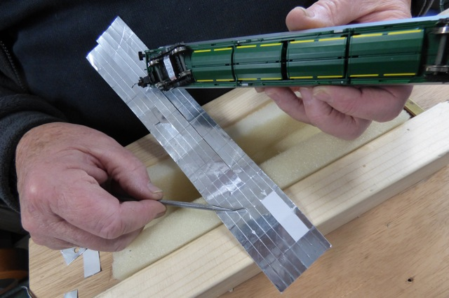 Aluminium Foil Tape on the bottom of a model train carriage - with tape slit to be fitted