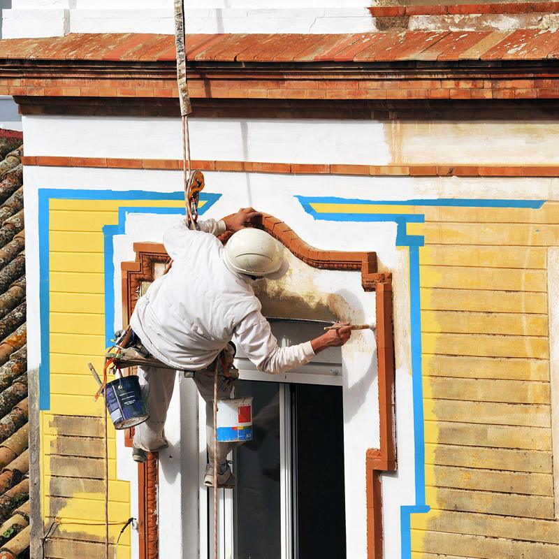 Professional painter and decorator hanging from building while painting on the 14 day blue tape